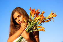 A Beautiful Teenage Girl With A Bouquet Of Orange Lilies Against A Blue Sky At Sunny Summer Day. Female Kid Of 10-12 Years Old. Wild Yellow Flowers. September 1, Back To School, Mother's Day Concept.