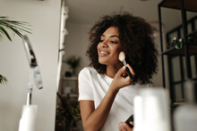 Attractive Lady Contouring Face. Dark-skinned Woman Holds Makeup Brush, Powders, Looks Into Mirror At Home.