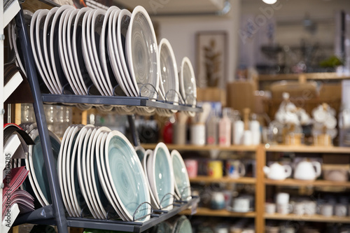 Fotografia Showcase with various new plates stacked on shelves in dishware department of su