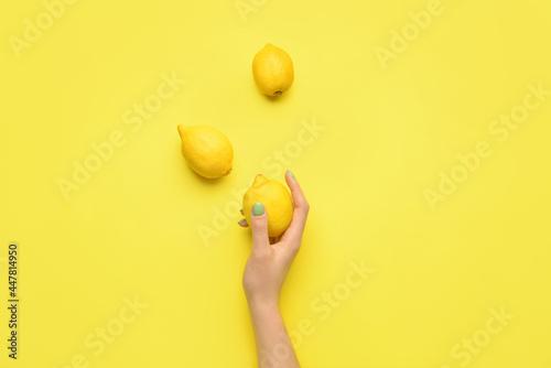 Fotografia Female hand with lemons on color background