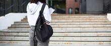 A Female Student With A Black Backpack And A Notebook In Her Hands Stands On The Steps In Front Of The University. Higher Education, The Beginning Of The School Year, Back To School. Copyspace