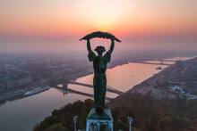Aerial View To The Statue Of Liberty With Liberty Bridge And River Danube At Background Taken From Gellert Hill On Sunrise In Fog In Budapest, Hungary