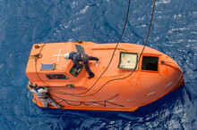 Seamen Hooking Up Lifeboat On The Sea