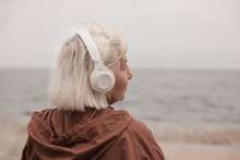 Side View Of Blonde Woman Wearing Headphones Listening Music Or Podcast From Smartphone Application Against The Sea