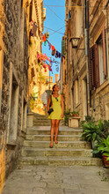 VERTICAL: Young Female Photographer Wanders Through The Sunlit Alleys In Korcula