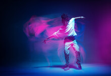 Stylish Dancing Modern Girl Moving In Colorful Neon Studio Light. Long Exposure. Copy Space