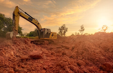 Backhoe working by digging soil at construction site. Bucket teeth of backhoe digging soil. Excavator digging on earth. Excavating machine. Earthmoving machine. Backhoe for rental business background.