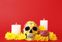 Painted Human Skull For Mexico's Day Of The Dead (El Dia De Muertos), Candles And Flowers On Color Background