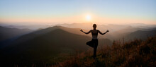 Panoramic View Of Woman Practicing Yoga On Background Of Evening Mountains. Meditating Female Is Balancing On One Leg At Sunset. Concept Of Balance.