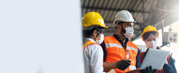 Engineers people are brainstorming solving problems of heavy industrial machinery. Worker man and asian woman wearing face mask prevent covid-19 virus and protective hard hat. .