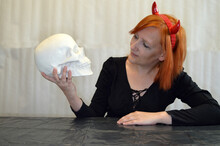 Young Red-haired Woman With A Plaster Skull In A Black Blouse With Red Horns On Her Head