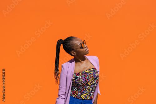 Canvas Print Chica africana con expresión relajada, en fondo naranja, con espacio para texto