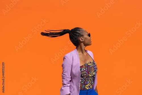 Wallpaper Mural Chica africana moviendo la cabeza en fondo naranja, con espacio para texto