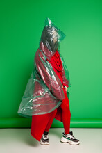 Calm Female Wearing Transparent Plastic Raincoat And Red Clothes Standing On Green Background In Studio