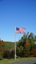 American Flag Blows In The Wind In This Autumn Scene.