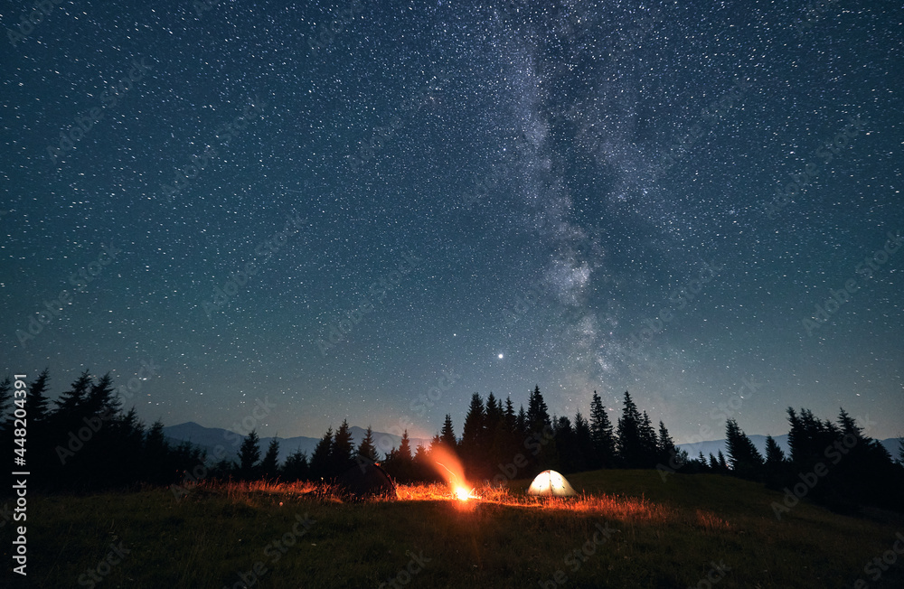 Wide angle view on beautiful landscape in the mountains. Tourist tents and campfire under beautiful starry sky. Mountains range behind spruces. Concept of night camping and astrophotography