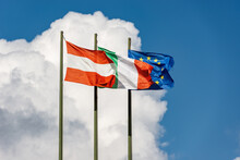 Austrian, Italian And European Union Flags With Flagpole, Blowing Togetherness In The Wind On A Clear Blue Sky With Clouds And Copy Space.