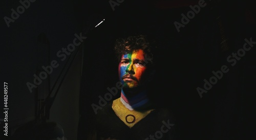 Fotografia Portrait of young man face painted as lgbtq progress pride flag with direct ligh