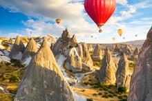Hot Air Balloons Flying Over Rocks Near Goreme Village. Cappadocia. Turkey