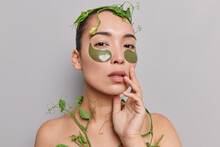 Portrait Of Brunette Young Asian Woman With Combed Hair Applies Hydrogel Patches Under Eyes To Reduce Wrinkled Wrapped With Green Climbing Plant Isolated Over Grey Background. Beauty Concept