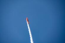 The Red Plane Makes Difficult Turns And Blows White Smoke Against The Blue Sky At The Max-21 Aerospace Salon In Zhukovsky On July 24, 2021