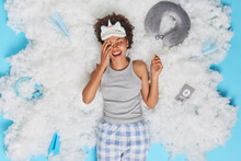 Overjoyed Curly Haired Afro American Woman Laughs Happily Dressed In Nightwear Has Upbeat Mood Poses On White Cloud With Passport Neckpillow And Paper Planes Around. Good Morning Welcome New Day
