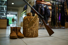 Rifle And Hunting Boots At The Stump In Gun Store
