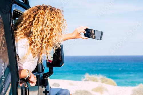 Obraz na plátně Happy travel woman and enjoy sea beach destination taking smart phone picture fr