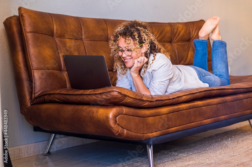 Fotografie, Obraz Adult woman lay down on te sofa and use laptop computer smiling and having fun a