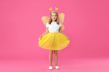 Cute little girl in fairy costume with yellow wings on pink background
