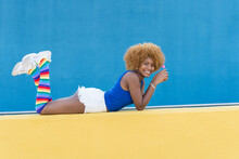 Happy Black Woman Lying On Yellow Border
