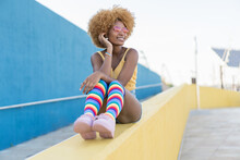 Delighted African American Woman Sitting On Yellow Border