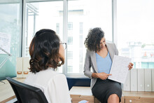 Confident Young Female Entrepreneur Showing Document With Ascending Line Charts To Her Colleague At Meeting