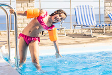 Pretty Little Girl Swimming In Outdoor Pool And Have A Fun