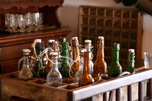 A Close Up On A Set Of Empty Glass Vintage Beer Bottles In A Wooden Crate And With Some Ropes Surrounding Their Necks Seen Inside Of An Abandoned Brewery On A Sunny Summer Day In Poland