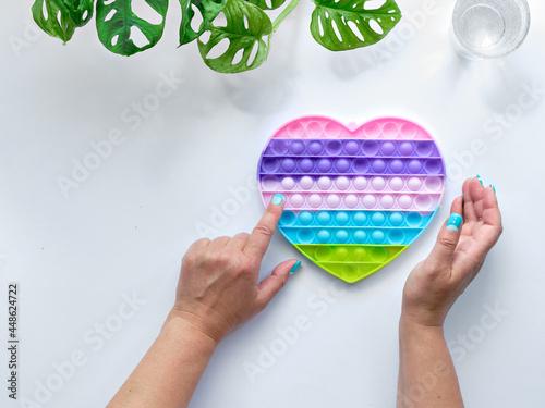 Heart shaped pope it antistress toy in female hands Fotobehang