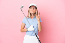 Young Golfer Player Woman Isolated On Pink Background With Fingers Crossing And Wishing The Best