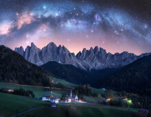 Santa Maddalena And Acrhed Milky Way At Night In Summer In Italy. Starry Sky With Milky Way Arch Over St. Magdalena And Mountains. Village With Houses, Church, Green Meadows, Trees, Rocks. Space