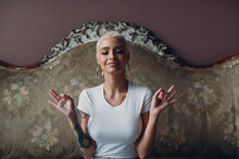 Millenial Young Woman With Short Blonde Hair Portrait Sitting And Meditate With Ok Sign Mudra On Vintage Sofa