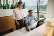 Manager standing by employee working in office