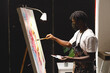 African american male painter wearing face mask painting on canvas in art studio