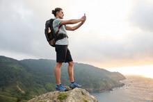 Traveling Man Taking Selfie On Hill Against Sea