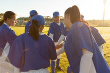 Diverse Group Of Female Baseball Players Warming Up On Field At Sunrise, Stacking Hands