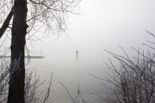 A Lonely Ice Skater On A Frozen Foggy Lake.