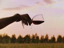 Close-up Of Hand Holding Glass Of Wine During Sunset