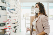 Woman Wearing Face Mask Shopping For Glasses