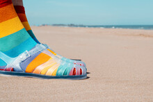 On The Sand Wearing Rainbow Patterned Socks And Sandals