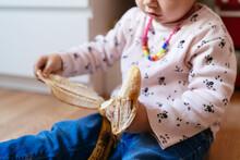 A Little Girl Peels A Banana