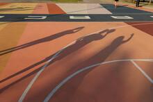 Shadows Of Children On A Reddish Basketball Court