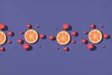 Creative Pattern Made With Strawberries, Orange Slices On Purple Background